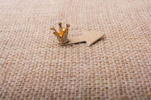 Mini crown and  a   paper arrow on canvas