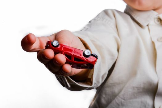 baby hand holding a red car on a white background
