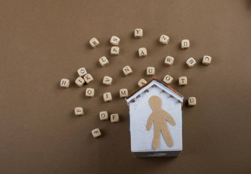 Wooden letter cubes   and man figurine and model house