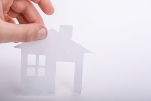 Hand holding an isolated paper house with a white background