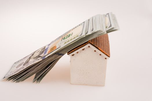 American dollar banknotes on the roof of a model house  on white background