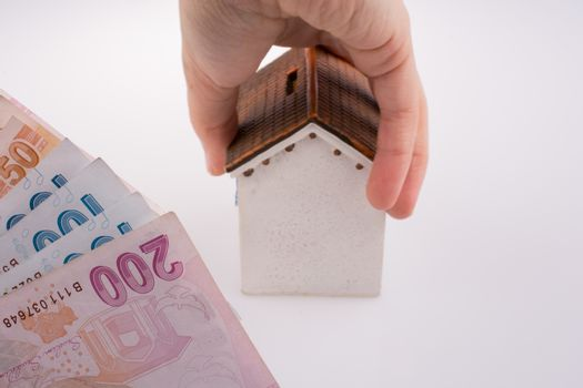 Hand holding  a model house by the side of Turkish Lira banknotes on white background