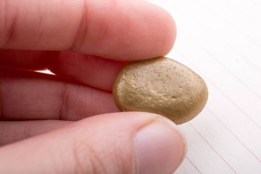Little gold color pebble in the hand