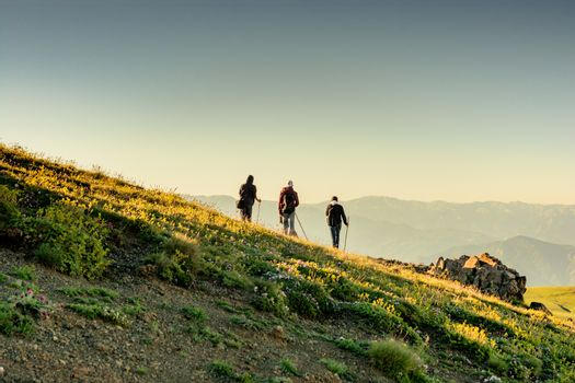 hikers with backpacks and trekking poles walking in Turkish highland