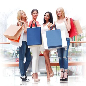 Four happy smiling young women with shopping bags posing in mall at sale