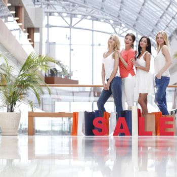 Women with red sale letters in mall , shopping concept