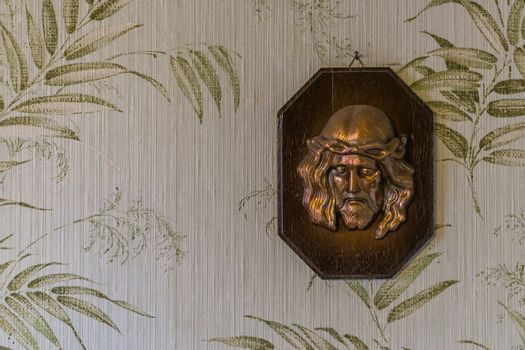 Face of jesus christ sculpture on a wooden plank, religious background