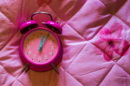 pink girly vintage alarm clock isolated on a pink blanket background