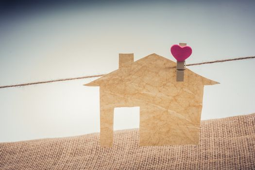Little paper house attached to a string with a heart clip