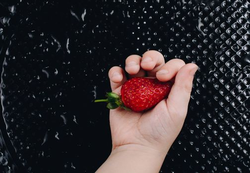 Juicy, sweet and ripe strawberry fruit in hand