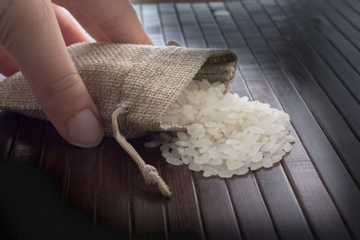 Hand holding straw pouch full of uncooked rice on a wooden background
