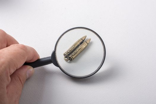 Bullet under magnifying glass as Conceptual against the war photography