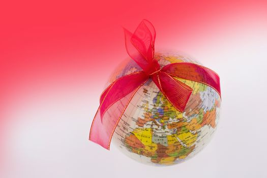 A globe with a ribbon on a reddish background