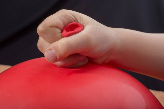 Toddlers hand holding a red balloon in hand