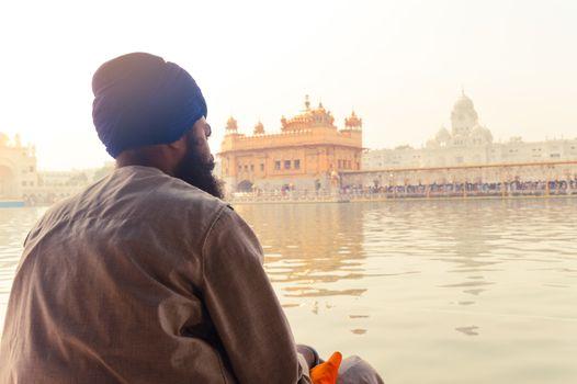 "Unidentifiable Punjabi Sikh pilgrim devotee ""Nihang Warrior"" sitting by the holy pool and meditating in front of Golden Temple (""Harmandir Sahib Darbar Gurudwara"") Amritsar, Punjab, India, Asia."
