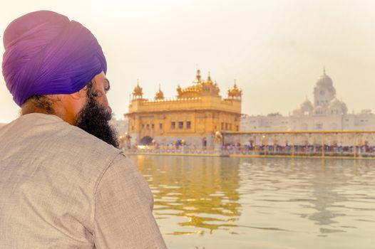 "Unidentifiable Punjabi Sikh pilgrim devotee ""Nihang Warrior"" sitting by the pool and meditating in front of Golden Temple (""Harmandir Sahib Darbar Gurudwara"") Amritsar, Punjab, India, Asia."