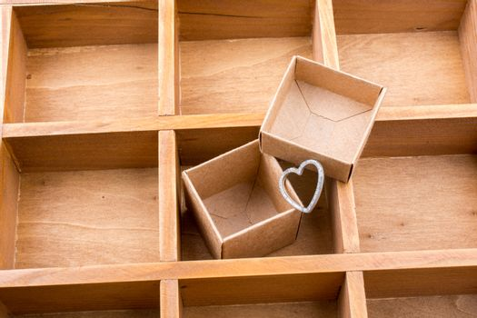 Cardboard box inside a wooden box with compartments and a heart