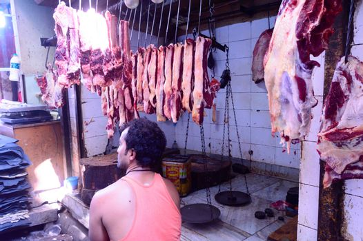 Burrabazar, Kolkata, India MAY, 2017: A seller is selling fresh raw red meat. Butcher shop for display. Burrabazar ( Bara Bazaar) is a marketplace, largest wholesale butchery markets store in India.