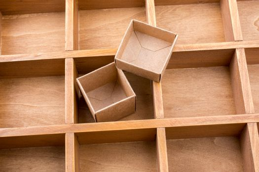 Cardboard box inside a wooden box with compartments