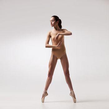 young beautiful ballet dancer in beige swimsuit