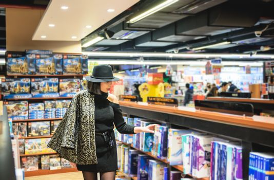 beautiful woman with black hat is in bookstore