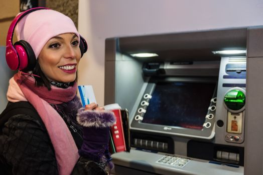 Beautiful woman in beanie pulls debit card