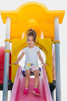 cute little girl trying to walk on slider