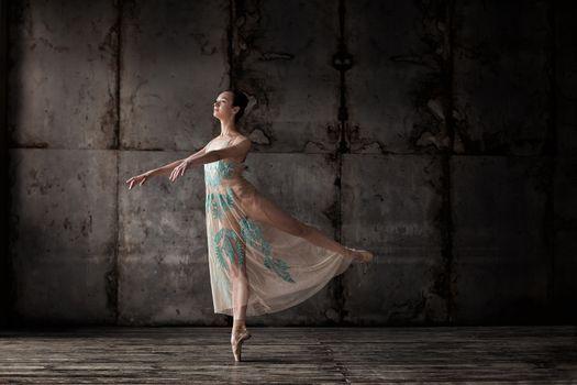 young beautiful ballet dancer in beige dress