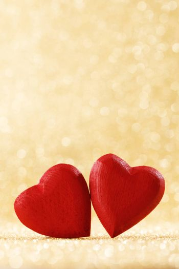 Two red handmade wooden hearts on golden bright glitter lights bokeh background