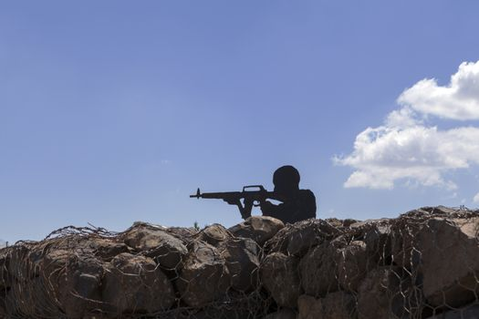 Soldier silhouette with blue sky in the background and rock reinforments in the foreground