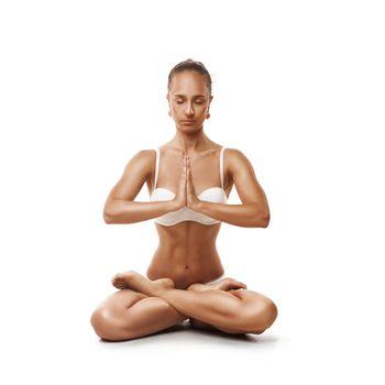 studio shoot of healthy latino woman doing yoga isolated over white
