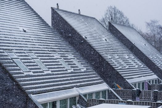 Modern pointed rooftops covered in snow, snowy and cold weather in winter season, new dutch house architecture