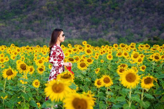 Young woman standing in a field of sunflowers.
