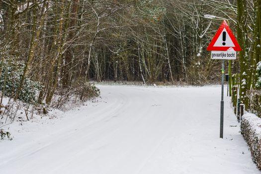 Dutch warning traffic sign, dangerous turn in bad weather condition, caution hazardous turn