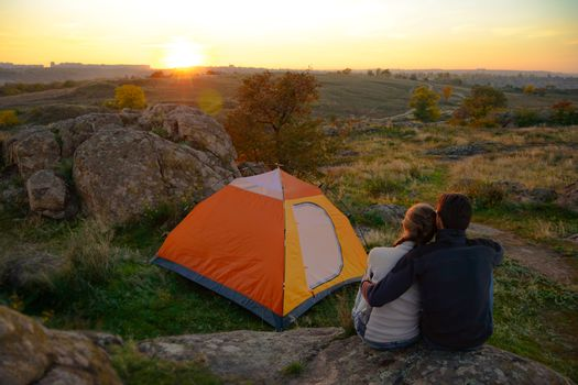 Young Couple Sitting near Tent and Watching Beautirul Sunset in the Mountains. Adventure and Family Travel.