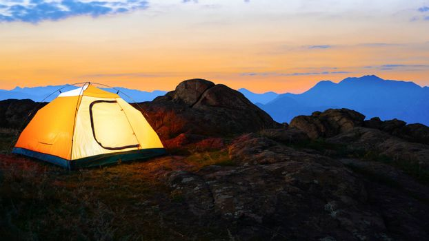 Yellow Illuminated Tent in the Beautirul Evening Mountains. Adventure and Travel.
