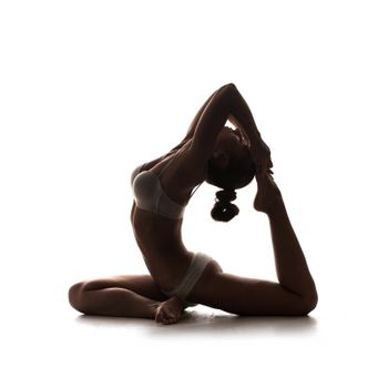 female silhouette of pigeon asana. young beautiful woman yoga posing on isolated white studio background