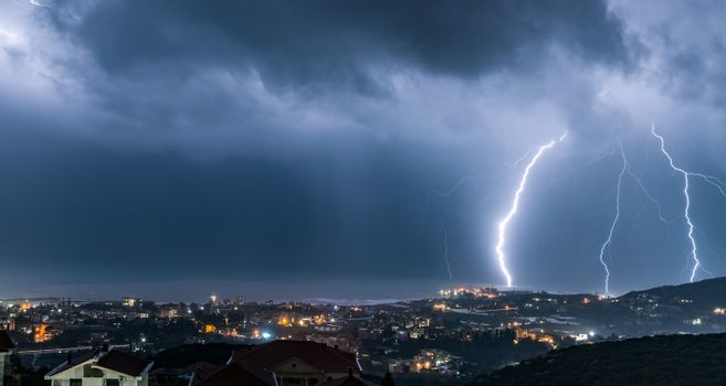 Night cityscape with lightning over it