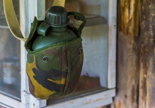 Vintage green drinking flask in a military printed bag, basic survival equipment