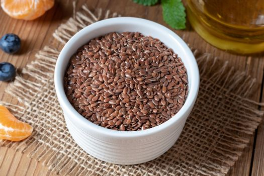 Flax seeds in a bowl, with flax seed oil in the background