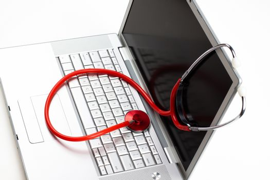 silver laptop diagnosis with red stethoscope isolated on white background