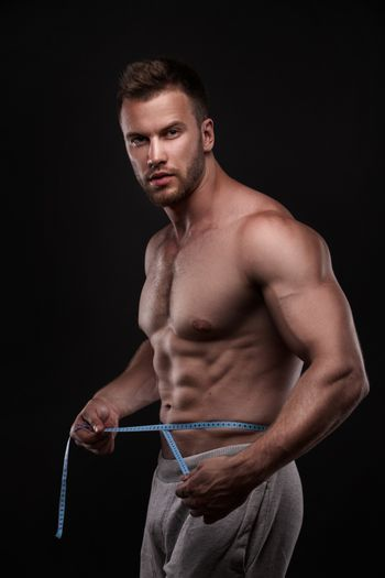 bodybuilder with a measuring tape around his stomach