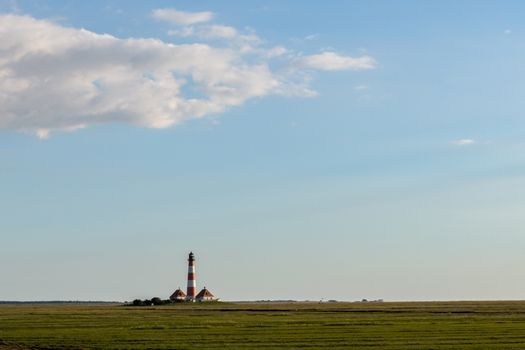 Lighthouse with salt marsh and copy space in blue sky