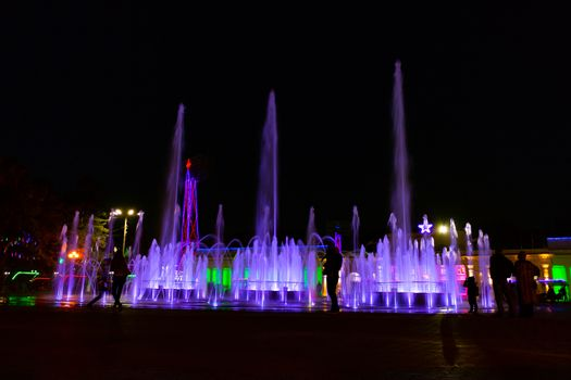 Bright colorful fountains at night on the embankment of the Amur river in the city of Khabarovsk. Bright color. Illumination of lanterns.