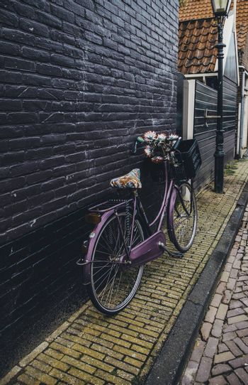 AMSTERDAM,NETHERLANDS - SEPTEMBER 06, 2018: Sunset in Amsterdam.Bicycle parking and traditional old dutch buildings.Flower market on Single canal, Netherlands
