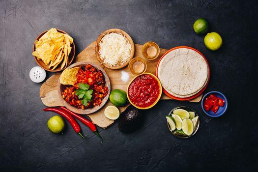 Concept of Mexican food (corn tortillas, nachos, salsa, avocado, limes, cheese, chili con carne) flat lay