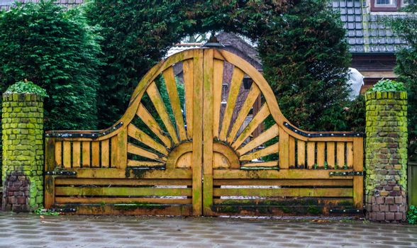 big and beautiful wooden garden gate with a sun pattern, modern outdoor architecture