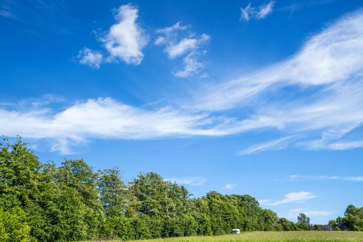 Camping trailer on a green field with blue sky in the summer