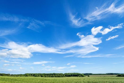 Landscape in a rural countryside environment in the summer with blue sky and funny clouds