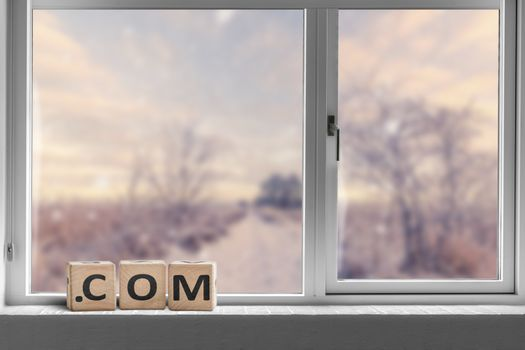 Com sign in a bright window with a view